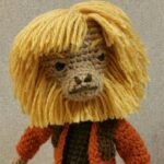 This is a closeup of a crocheted Dr Zaius character doll.