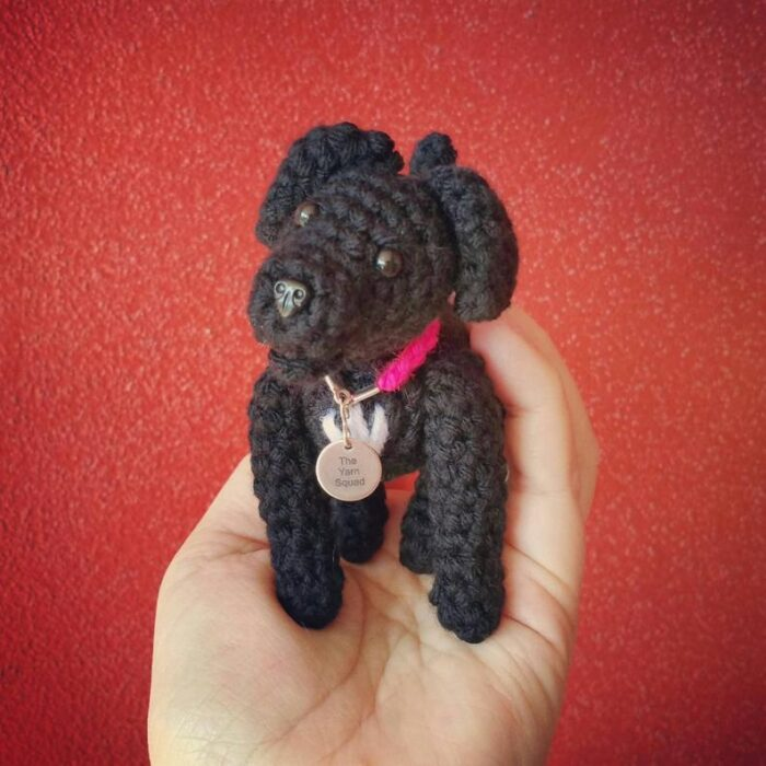 Black crochet dog doll sitting in the palm of a lady's hand