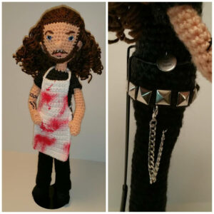 Male crochet doll wearing black with a white apron splattered with red paint