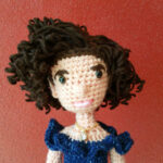 Portrait view of a crochet doll with brown curly hair