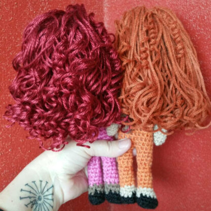 Back photo of 2 crochet dolls with red and orange hair