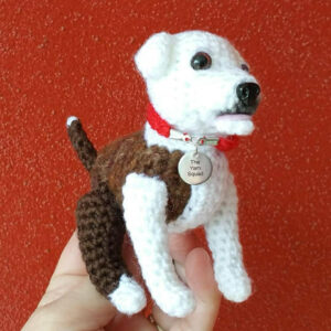 White and brown crocheted dog doll with a red collar